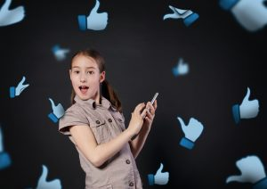 Children addiction to social networks. Portrait of little girl surprised touching screen of mobile phone at black background. Child and thumb up icons fly around. New generation device, communication